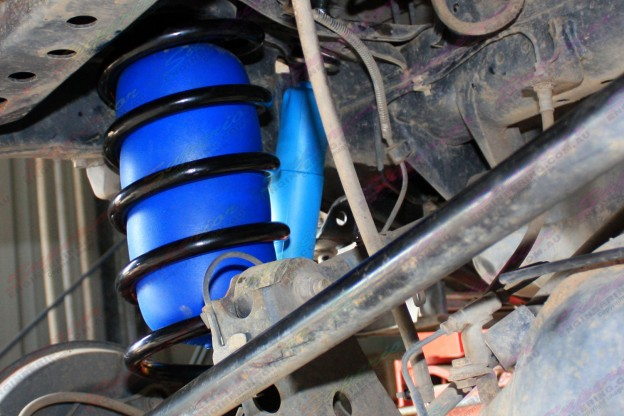 Close up view of some fitted coil helper airbags in side some heavy duty 100 Series coil springs