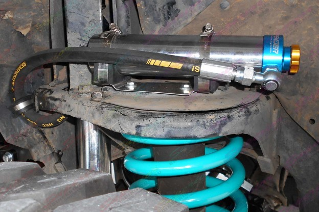 Profender 4x4 Remote Res shock mounted to the top of the coil tower and some heavy duty blue coil springs