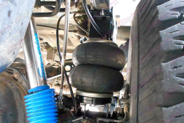 Closeup view of a single leaf helper spring and air hose and superior shocks fitted to the 76 Series Landcruiser