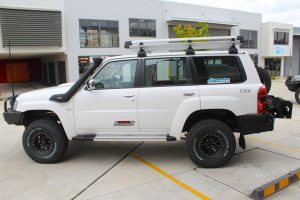 Left side view of a white GU Nissan Patrol Wagon after being fitted with a full 2 Inch Superflex Lift Kit featuring Airbag Man airbags