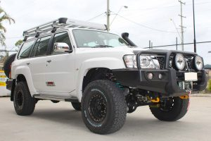Front right view of a white GU Nissan Patrol Wagon after being fitted with a full 2 Inch Superflex Lift Kit featuring Airbag Man airbags