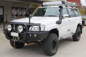 Front left view of a white GU Nissan Patrol Wagon after being fitted with a full 2 Inch Superflex Lift Kit featuring Airbag Man airbags