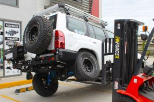 Rear view of the boys testing out the flex of the GU Nissan Patrol wagon with the forklift at the front of the Superior Engineering 4x4 retail showroom at Deception Bay