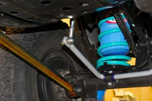 Closeup underside view of the rear end of the GU Nissan Patrol showing the Airbag Man airbag, coil spring, lower control arm and swaybars