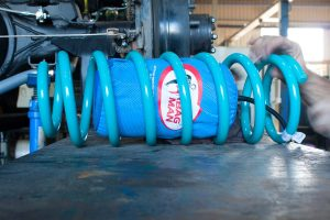 Closeup view of the Airbag Man airbag being fitted inside a single Dobinsons coil spring on the hoist at the Superior workshop