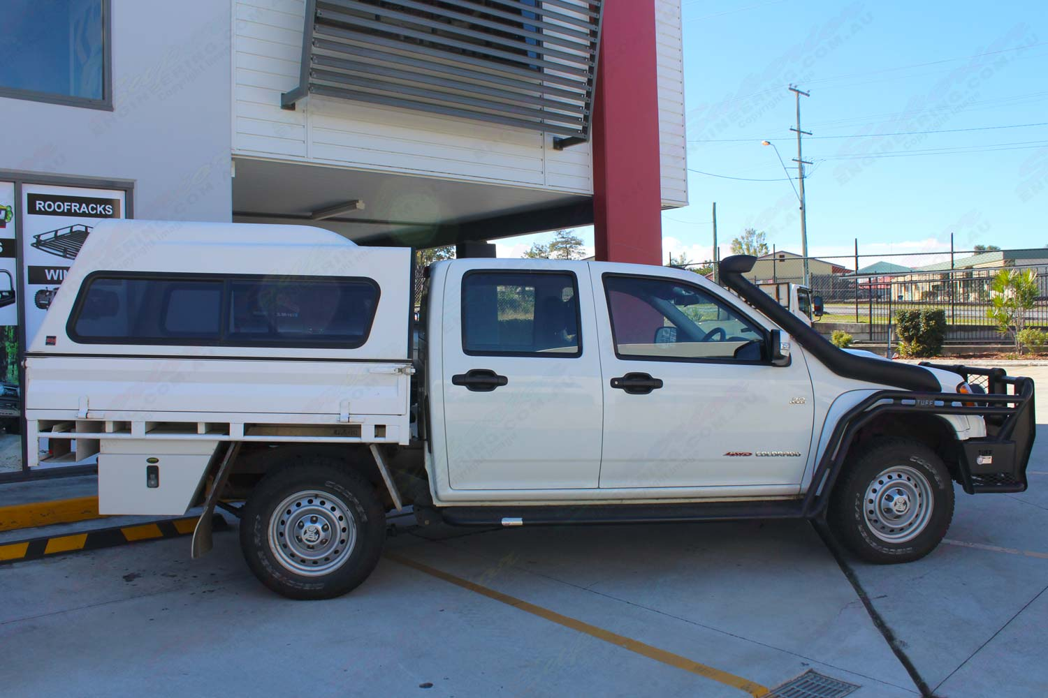 Right side view of a white Holden Colorado dual cab fitted with a 40mm Bilstein lift kit and AirBag Man air suspension helper kit for leaf springs